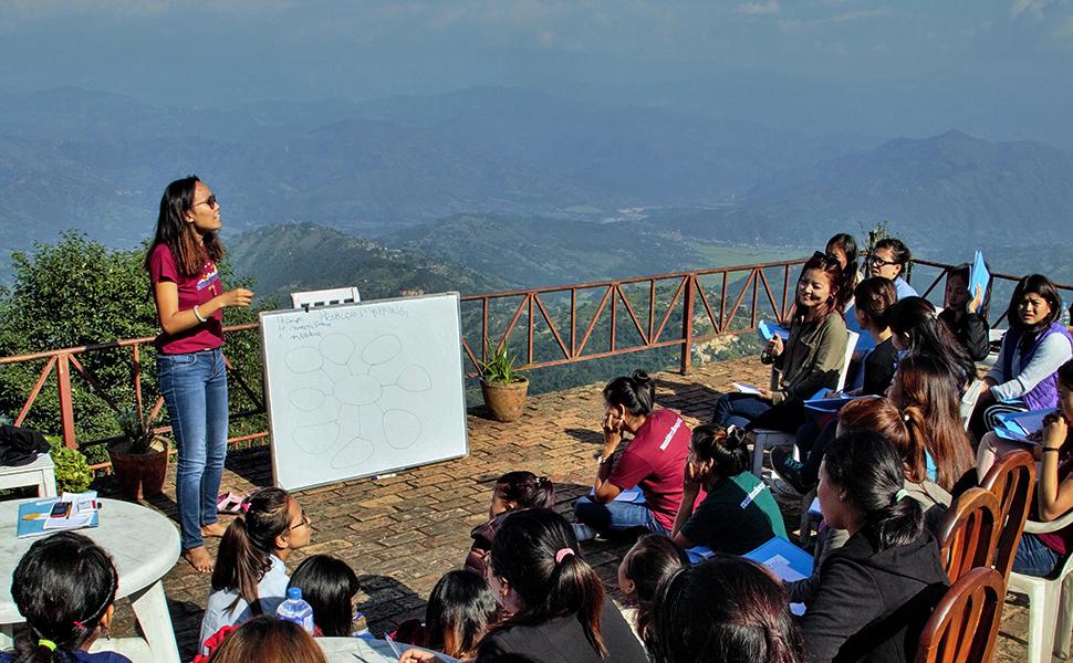 Tsechu Dolma (standing) at a community meeting in Nepal